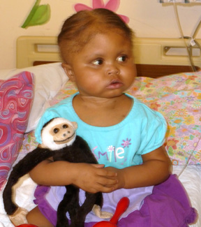 A Rainbow Babies and Children's Hospital patient with the first name of Za'Nyha holds a monkey she received while in the hospital.